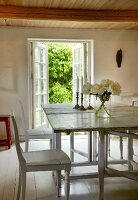 White wooden table and chairs in dining room with white wooden floor