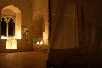 Unique ambiance in candle-lit bedroom in Chateau Maignaut with canopied bed and ancient masonry