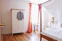 Bright bedroom with white wardrobe and canopied bed