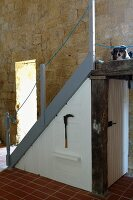 Australian Shepherd on landing of staircase with integrated cupboard in front of sandstone wall (Chateau Maignaut)