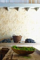 Dish of leaves on joiner's workbench and bunches of grapes against ancient sandstone wall (Chateau Maignaut)