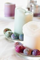 Candles wreathed with colourful snail shells on dining table