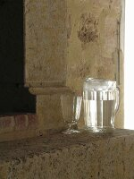 Jug of water and glass goblet in front of fireplace within ancient sandstone walls
