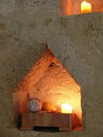 Candle in pointed niche in ancient sandstone wall