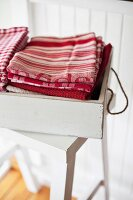 Stacked dish towels in a white vintage box on a stool