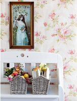 Framed photograph above baskets of garden roses on white wooden bench against rose-patterned wallpaper
