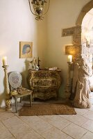 Baroque chest of drawers and chair next to candelabras on floor in corner of room in Mediterranean country house