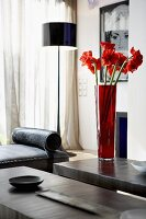 Cut flowers in red vase on grey coffee table in modern living room setting