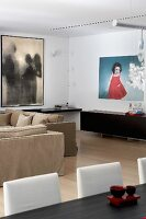 Contemporary paintings and sideboard in modern living room with pale parquet floor
