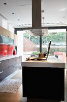 Contemporary designer kitchen with black island in front of glass wall