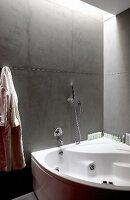 Corner bathtub with whirlpool jets in modern bathroom with grey stone walls and indirect ceiling lights