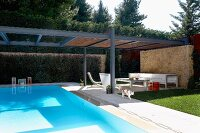 Roof over pool and designer terrace seating area with stone wall
