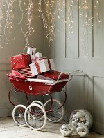 Christmas presents in red pram below fairy lights