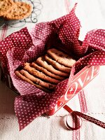 Chocolate chip cookies in a biscuit tin lined with a red and white napkin