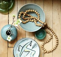 Assorted Items on a Table' From Above; Strand of Wooden Beads, Small Vase with Flowers and a Decorative Plate