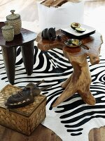 Small carved wooden table with African ornaments on zebra skin rug