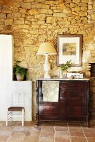 Antique chest of drawers against rustic stone wall in Mediterranean interior