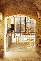 View of simple dining area in kitchen flooded with light seen through arched open doorway in stone wall