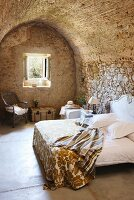 Rustic bedroom with stone walls and vaulted ceiling