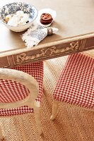 Dining table and chairs with red and white hound's-tooth check upholstery on herringbone rug