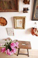 Pictures and boxing gloves on wall above old stool and bouquet of peonies