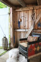 Old leather armchair with combination of fabrics in front of open door of wooden cabin