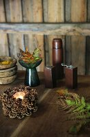 Small pine cone wreath, fern leaves, salt cellar and pepper mill on rustic wooden table