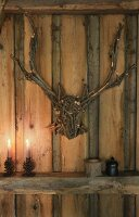 Stag's head and antlers made of twigs and pine-cone candlesticks on wooden beam