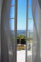 View of gardens and expansive landscape through open French windows with wafting curtains
