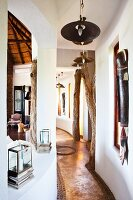 Curved hallway with tree trunks as ceiling props and ethnic artworks on walls