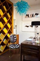 Yellow books in original shelving unit; pretty, blue glass lamp in foreground above Baroque chair with zebra skin upholstery