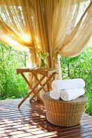 Sunny spa area with rattan table and stool; rolled white towels on stool