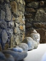 Collection of stones next to head of Buddha on shelf against stone wall
