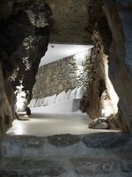 View from below through cave-like, interior corridor to white, masonry bench with cushions against stone wall