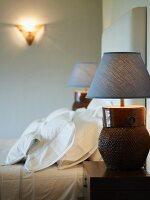 Bedside lamps with blue fabric lampshades and basket-like bases on bedside tables either side of bed
