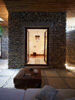 Rustic coffee table on terrace in front of stone extension with open door and view into illuminated bathroom