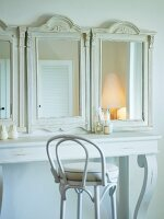 White dressing table with three antique mirrors on top and white-painted Thonet chair