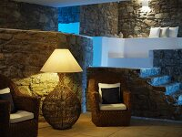 Rustic interior with stone walls and lit standard lamp between two wicker armchairs