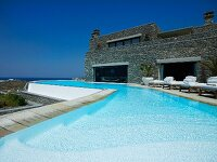 Pool complex with sun loungers in front of modern Mediterranean farmhouse