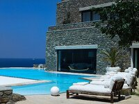 Pool and sun loungers in front of modern Mediterranean farmhouse with sea view