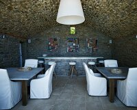 Chairs with white covers in seating area in cellar-like room with vaulted stone ceiling