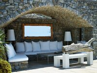 Arched niche with bench and white cushions in stone house facade