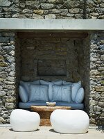 Niche in wall of stone house with built-in bench and white modern stools