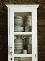 Crockery in white, shabby chic, glass-fronted cupboard against stone wall
