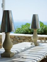 Table lamps with stylised concrete bases and metallic lampshades on stone table