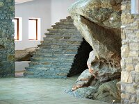 Rough, unhewn rock and finished stone fixtures in modern foyer