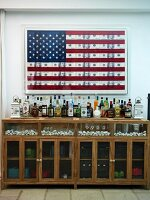 Half-height drinks cabinet with glass doors below stylised American flag on wall