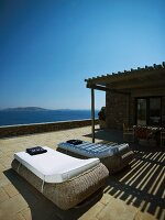 Relaxation area on sunny terrace- sun loungers with white cushions and a sea view