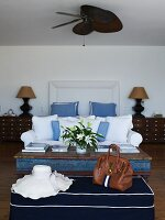 Lady's hat and handbag on ottoman in front of coffee table and white sofa in bedroom
