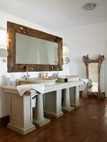 Antique-Greek-style washstand below wall-mounted mirror with rustic wooden frame in modern bathroom